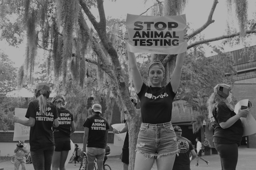 black and white image of protester hold a Stop Animal Testing sign