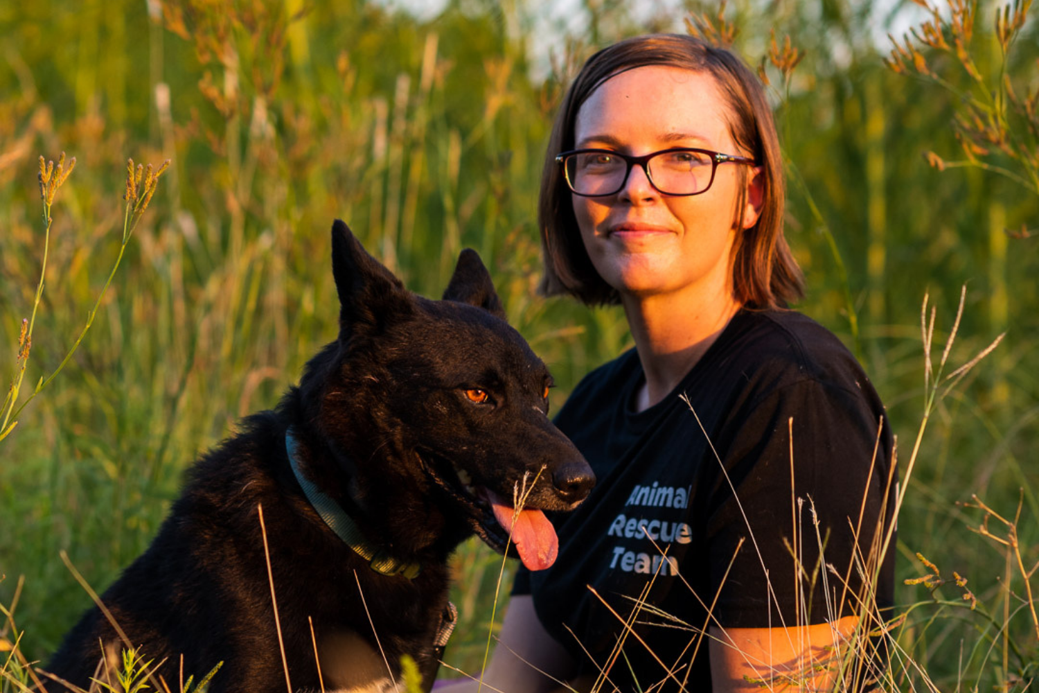 Amy Meyer sits in tall, sunlit grass with Astro, a dog she helped rescue with Rise for Animals